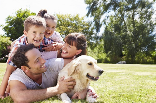 family embracing with their dog
