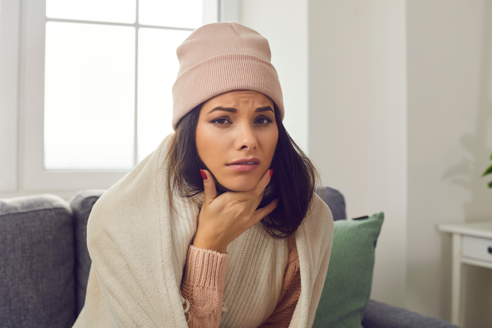 Sick young woman in warm hat and blanket suffering from sore throat